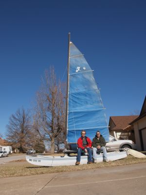David Massey (right) and I are seated on this winters project, rehabbing a 14 foot Hobie Cat.o The old Hobie Cat languished in a friends field for the last thirteen years. Major work was done to rusted trailer an we have now undertaking repairs to the boat. Rudders, rope lines, trampoline and a new sail are needed.