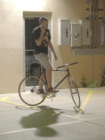 Matt practices his track stands while checking his messages.