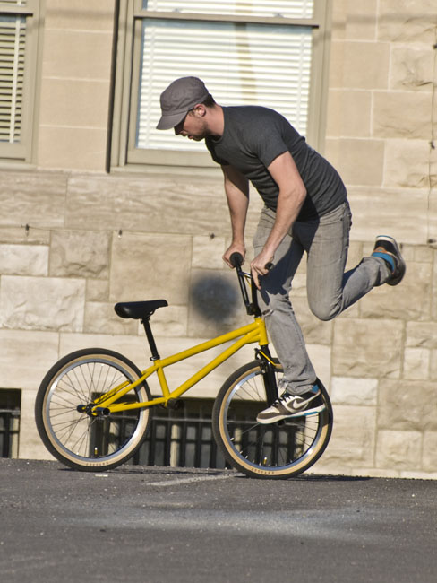 A bicyclist practices his flat land freestyle moves.