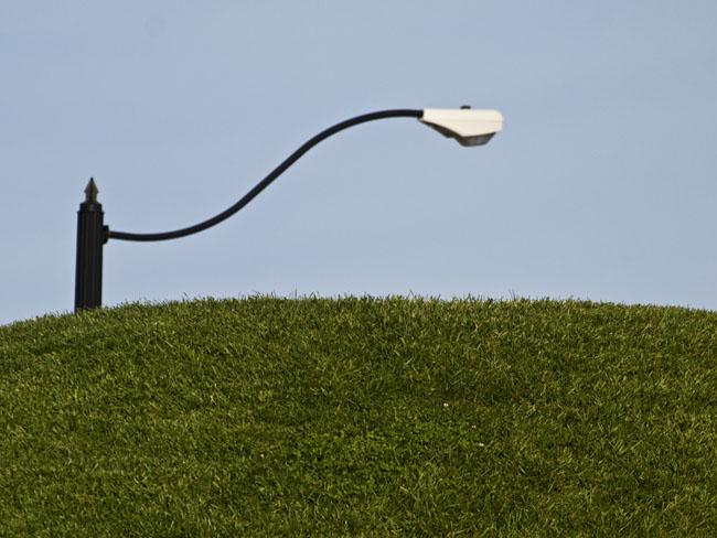 A hillside berm and an electric street lamp