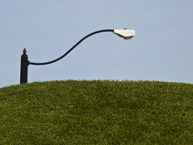 A hillside berm and an electric street lamp