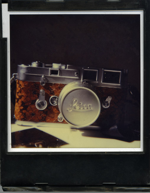 An SX-70 Polaroid photograph of a snakeskin covered Leica M-3 double stroke.