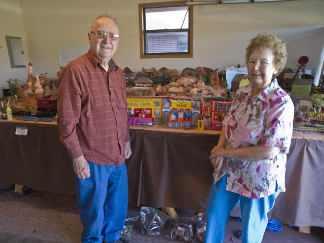 Raymond and Lorene Richardson stand in front of his Kansas railroad diorama and the the circus wagons of C.W. Parker.