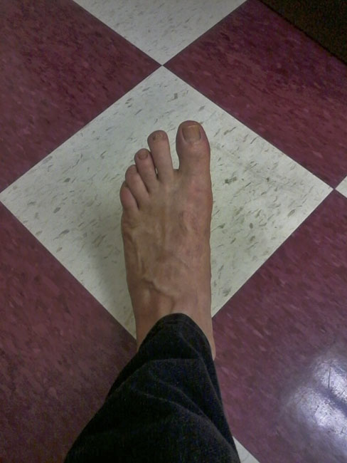 My left foot on tiles of red and white