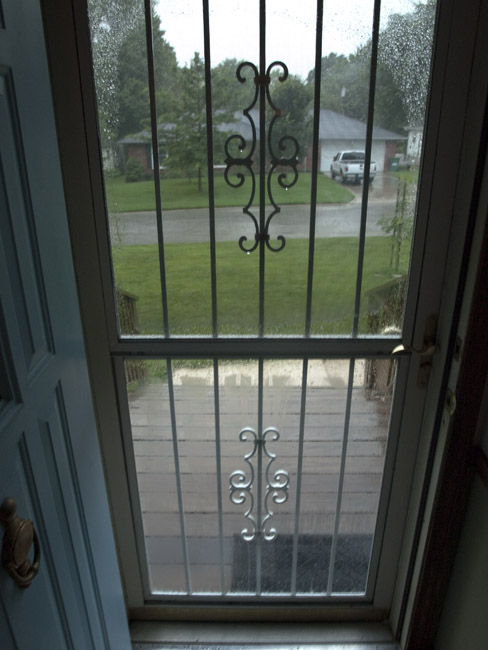 An open front door and the sound of the pouring rain