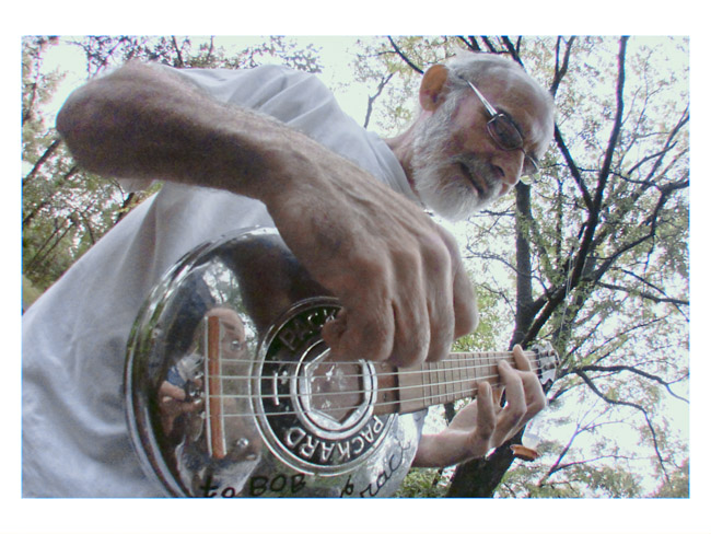 "Bob Runyon on his back deck with the ""Jim Cracker Reed"" Packard hubcap ukulele."