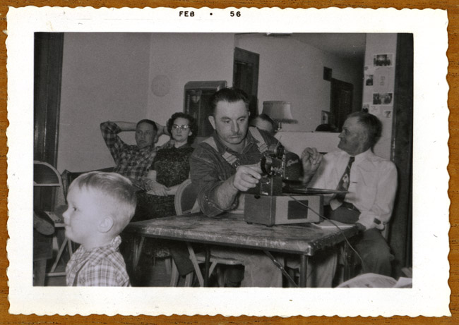 My Grandfather Dominic Bernard  loaded the filmstrip projector on Christmas Day, 1955. Family from left to right are A smiling Gaylen Bagby, Ivan and Eddie Peterson,  Dominic Bernard Radke and Uncle Charlie Peterson