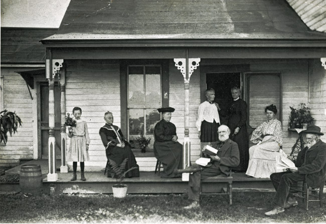 Kingston Family Portrait. Left to right; Essie Kingtson with a handful of flowers, Mary Ellen Kingston wearing a white blouse, John Willard Kingston is seated on the right.