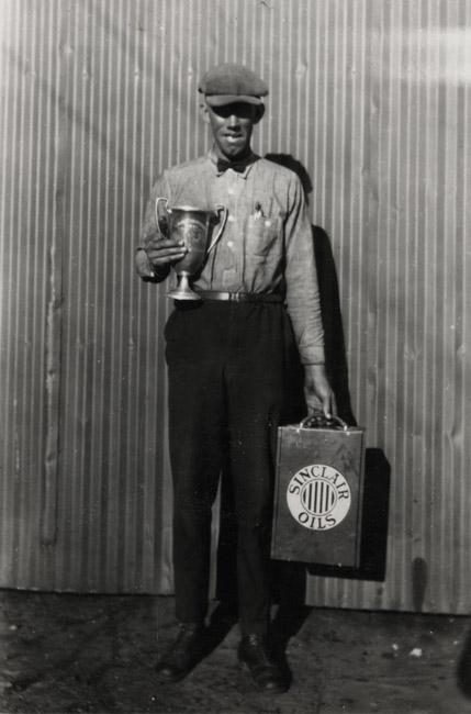Portrait of Walt Sprick with his quota Trophy and Sinclair Oil can.