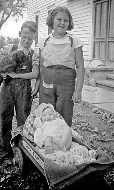 Billy Guidinger held Poochie the dog, Toni Guindinger kicked back in the Pony Express wagon, and Betty Guidinger. circa 1938